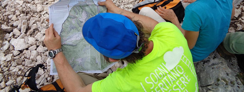un escursionista studia il percorso sulla cartina