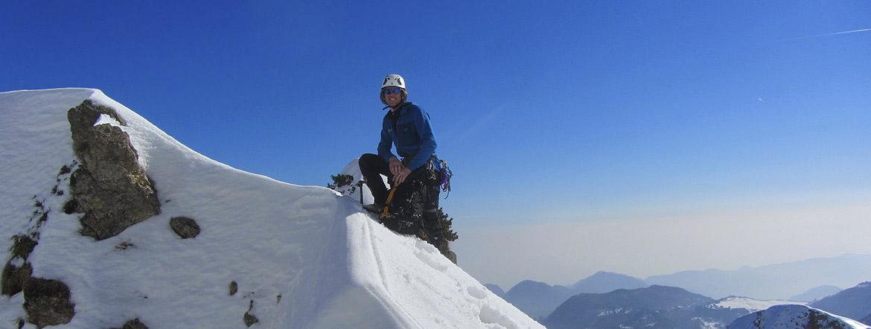 Andrea basso viene immortalato mentre raggiunge la vetta di una montagna innevata
