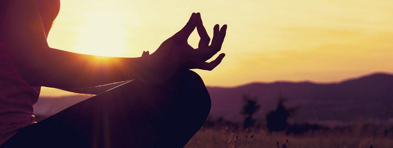 foto artistica scattata al tramonto, con una donna che fa meditazione